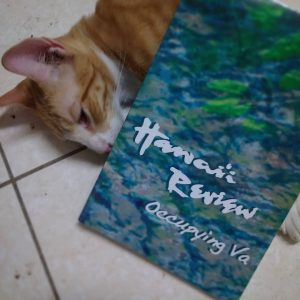 an orange kitten with a copy of Hawai'i Review: Occupying Va