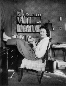 Anne Sexton, leaning back on a chair, in front of a desk with a typewriter and many books.